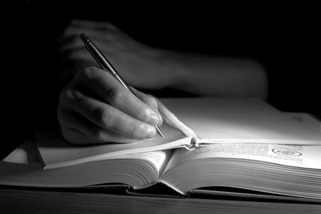 Open book in a dark room, with uman hand taking notes Stock Photo - 1778911