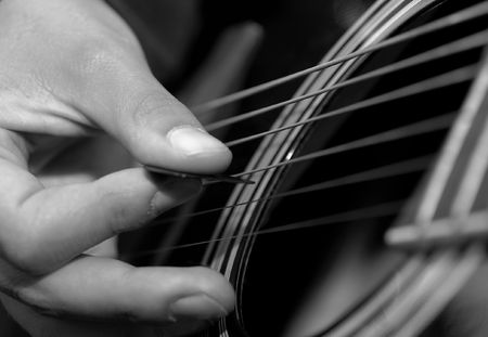 Hand picking a black acoustic guitar photo