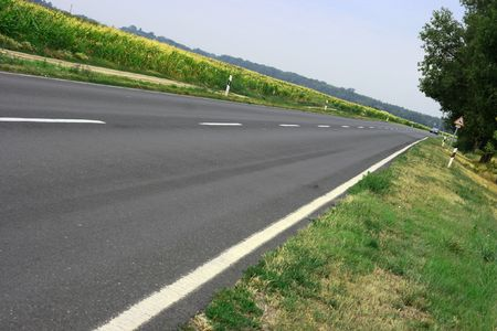 Asphalt road going through the countryside photo