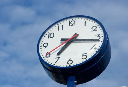 analogue: Big analogue clock against blue cloudy sky