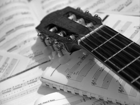 sheetmusic: Head and neck of an acoustic guitar with sheet music Stock Photo