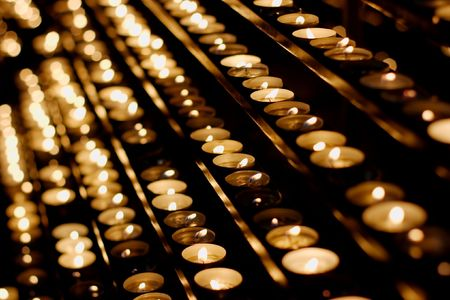 cultic: Rows of burning candles in a dim church Stock Photo
