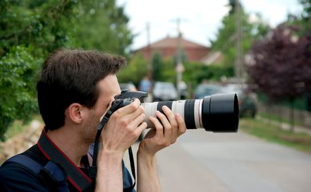 Photographer taking pictures with a telephoto lens photo