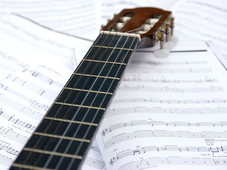 sheetmusic: Acoustic guitar head and neck over sheet music