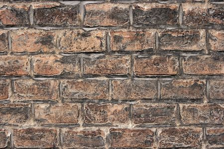 Old grungy brickwall with rough brown bricks photo