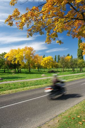 Motormike rider passing by with motion blur in an autumn landscape Stock Photo - 1979346