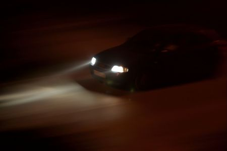 Car going fast in the night, rays of light from the headlights photo