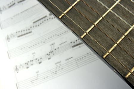 sheetmusic: Closeup of the neck of a guitar and music score in the background