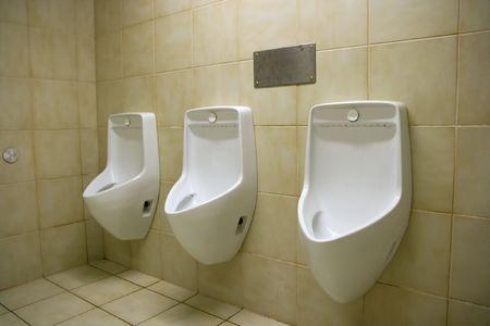 Three urinals in a public toilet