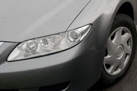 Headlights and wheel of a wet gray car photo
