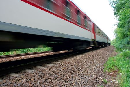 Fast passenger train passing by with motion blur photo