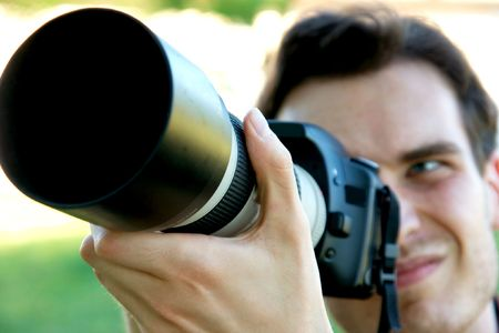 Photographer using his camera with telephoto lens photo