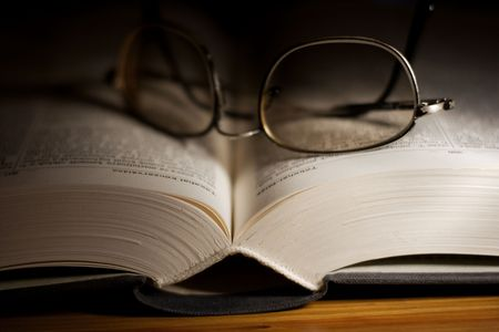 Thick open book in the dark with glasses on it Stock Photo - 2330083