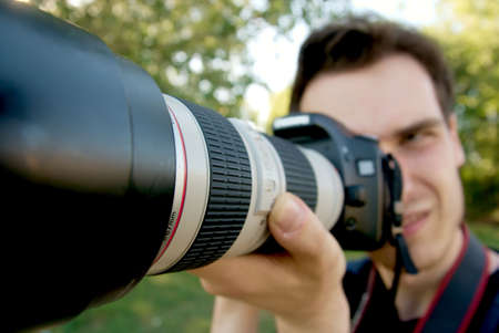 Portrait of a photographer taking pictures with a telephoto lens photo