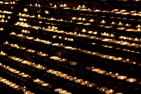 cultic: Rows of burning candles in a church