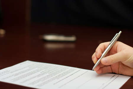 Hand with a pen about to sign a contract photo