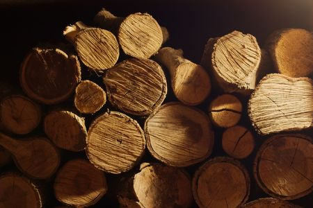 A pile of logs in the night at the light of a lamp photo
