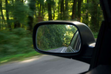 Sideview mirror of a car driving on the road Stock Photo