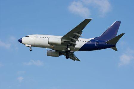 White avion commercial battant contre ciel bleu  Banque d'images