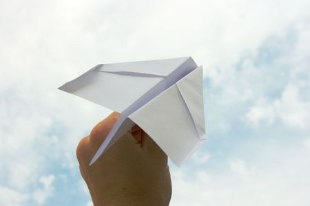 Hand holding a paper plane made of white sheet photo