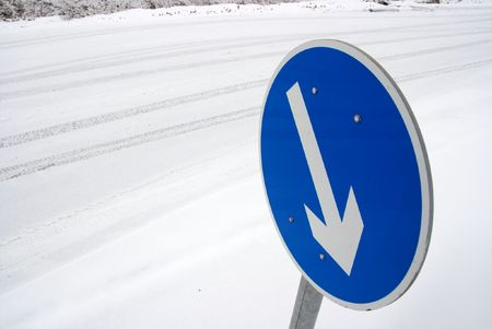 Arrow sign on a road covered by snow photo