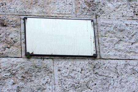 Empty signboard on a stone wall. Add your own text! photo