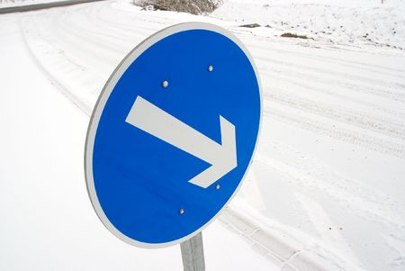 Arrow traffic sign on a snowy road photo