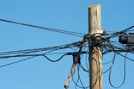 Lots of messy wires on a wooden pillar photo