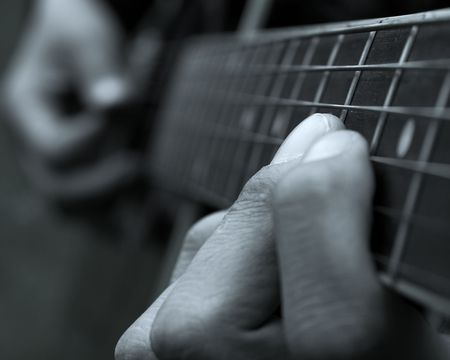 Closeup of the fingers of a guitar player photo