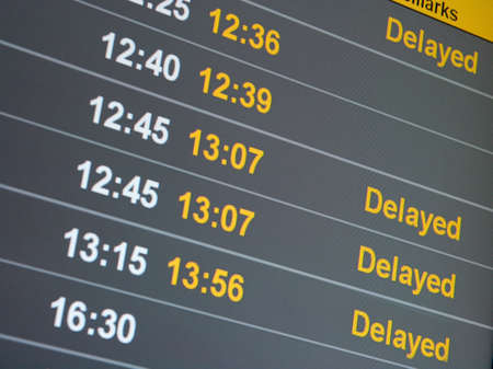Many delayed flights on the departure table of an airport photo