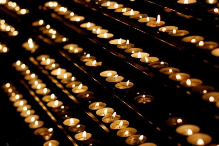 cultic: Rows of candles in a dim church