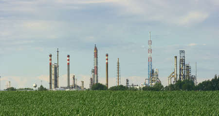 Oil refinery over a green agricultural field photo