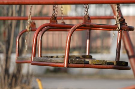 Closeup of aged swings on a playground photo