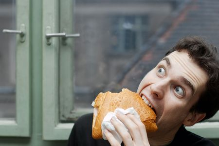 devour: Man eating with silly expression