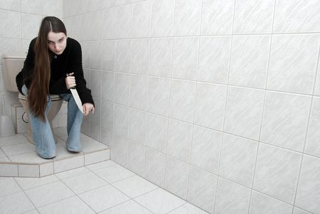 wicked problem: Girl sitting in the bathroom with knife in hand Stock Photo