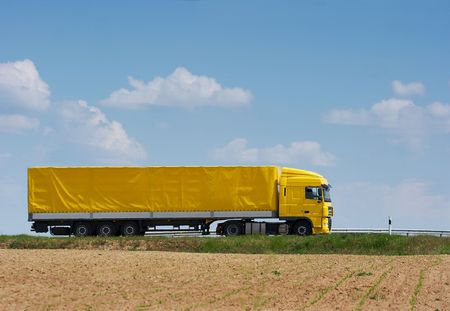 truckload: Yellow truck going on the highway Stock Photo