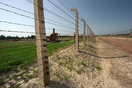 Ruins and barbed wire fences in Auschwitz photo