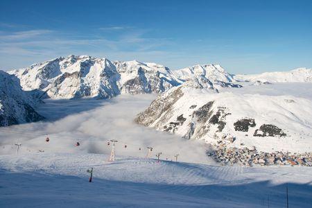 High mountains with ski tracks and ski lifts photo