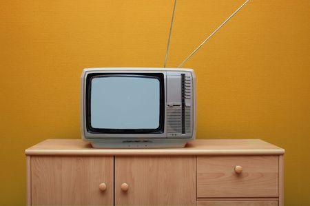old fashioned tv: Vintage TV set, orange wall Stock Photo