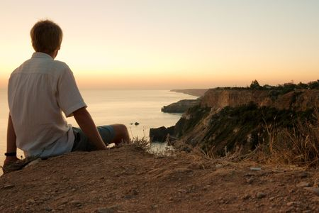 Man sitting on the edge of a cliff, staring at a majestic coastline photo