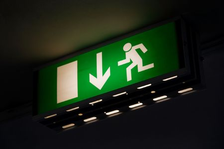 Emergency exit sign glowing green in the dark photo