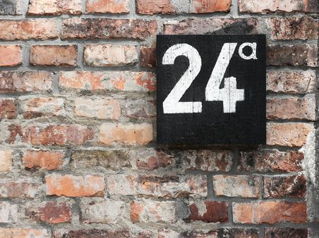 Brick wall with number on a board photo