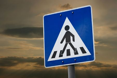 Pedestrian crossing traffic sign against twilight sky photo