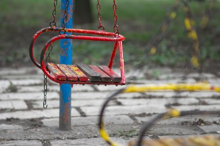Old red swing on a playground photo