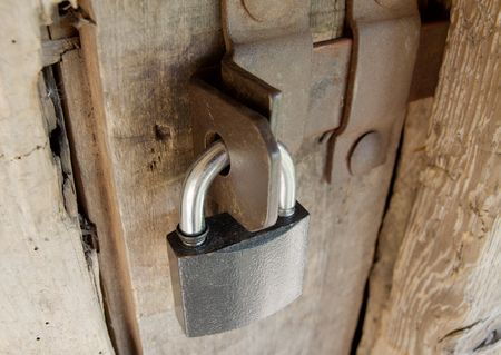 Padlock on an old wooden barn door photo