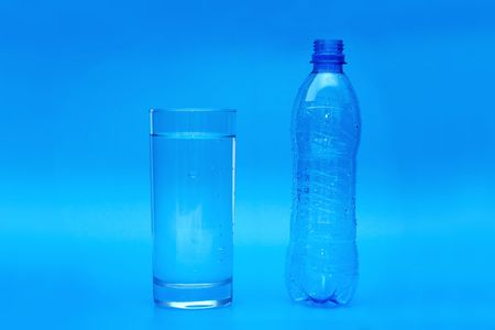 Full glass and empty bottle on blue background photo