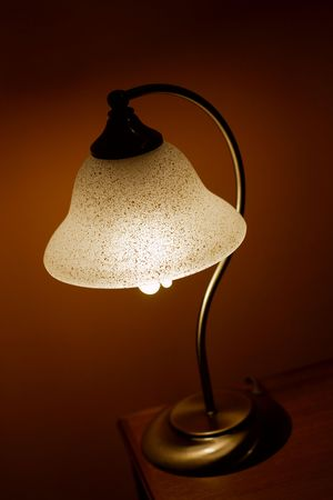 Small lamp glowing in a dark room photo