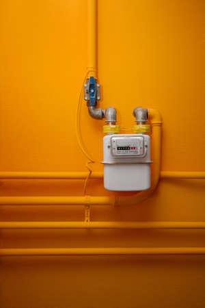metro medir: Las tuberías y contadores de gas en la pared de color naranja