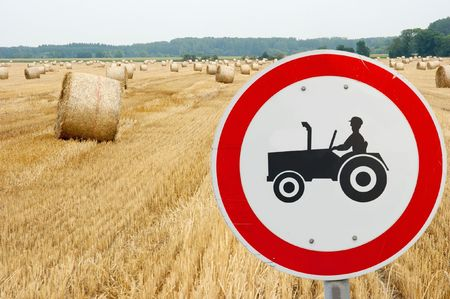Tractor traffic sign in front of an agricultural field photo