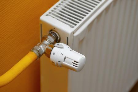 save heating costs: Heating radiator detail against orange wall